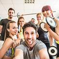 Ein Mann macht ein Selfie von mehreren Frauen und einem Mann in Sportklamotten und mit Hanteln