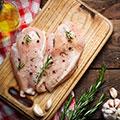 Ein Stück gewürztes helles Fleisch liegt auf einem Holzbrett umgeben von Kräutern und Öl