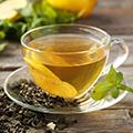 Gläserne Tasse und Untertasse mit Tee und einer Zitronenscheibe