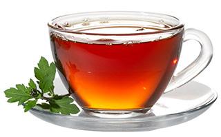 Rotgoldener Tee in einer Glastasse mit Untertasse auf weißem Hintergrund