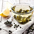 Durchsichtige Teetasse mit grünem Tee und Teeblättern gefüllt mit Zitrone und Teelöffel daneben liegend