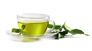 Durchsichtige Teetasse mit grünem Tee gefüllt und Teeblättern auf weißem Hintergrund