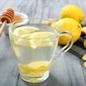 Durchsichtige Teetasse mit Wasser und Zitronenscheiben auf hölzernem Untergrund von Zitronen und Honig umgeben