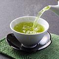 Weiße Tasse in die mit einer Teekanne grüner Tee eingegossen wird auf grünem Tuch