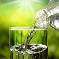 Wasser wird vor grünem Hintergrund aus einer Flasche in ein Glas eingeschenkt