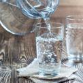 Zwei Wassergläser stehen auf einem hölzernen Untergrund und in eines wird aus einem Glaskrug Wasser eingeschenkt