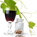 Gefülltes Weinglas neben einer kleinen Schale mit Kapseln und der zugehörigen Verpackung