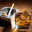 Whiskey im Glas mit Eiswürfeln neben einem gefüllten Aschenbecher