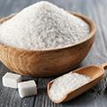 Zucker in einer Holzschale, daneben zwei Stück Würfelzucker