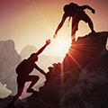 Zwei Bergsteiger reichen sich die Hand während dem Aufstieg mit Sonnenuntergang im Hintergrund