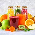 Zwei Gläser mit rotem und orangem Smoothie und dahinter drei Flaschen gefüllt mit Smoothies umgeben von Obst