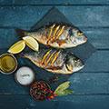 Zwei gegrillte Fische liegen mit anderen Zutaten auf blauem hölzernen Untergrund